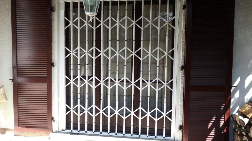 Scherengitter vor Holzfenster und zwischen Klappladen